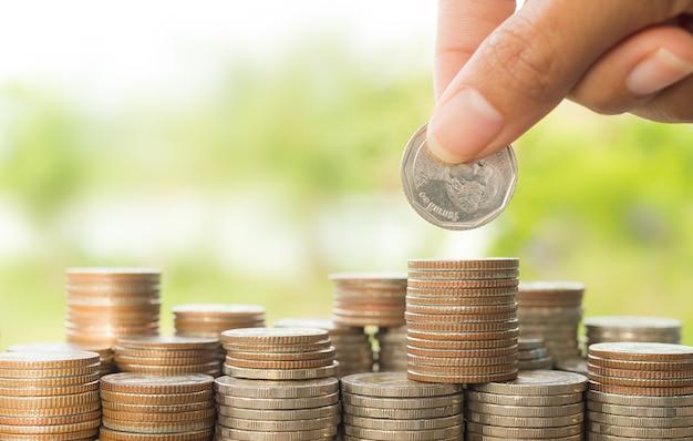 Plan oszczędzania pieniędzy. dłoń trzymająca monety na stosie monety pieniądze z zielonym rozmyciem tła.