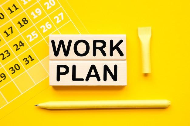Plan pracy. kalendarz i drewniane baby z informacją na żółtym tle pulpitu.