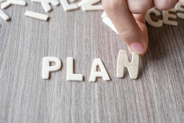 Plan słowo drewniani abecadło listy. koncepcja biznesowa i pomysł