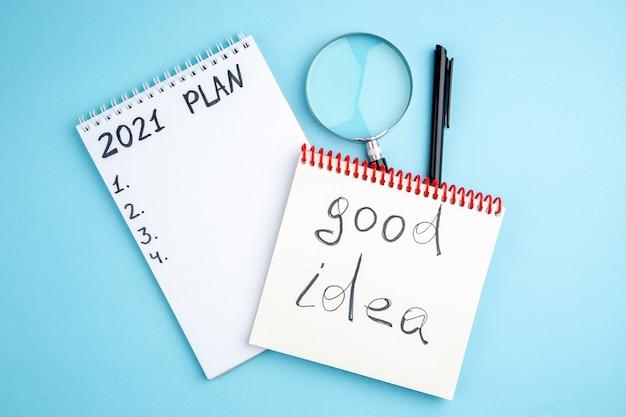 Plan widoku z góry i dobry pomysł napisany na spiralnych zeszytach długopis lupa na niebieskim tle
