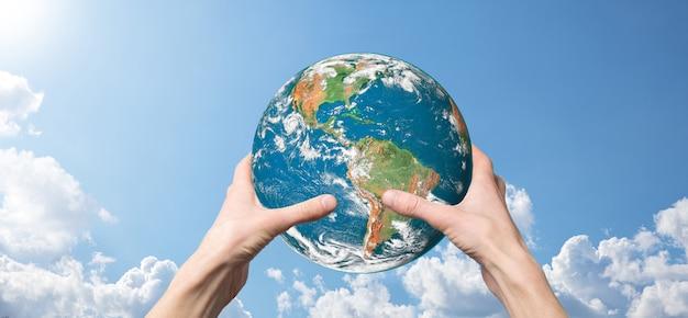 Planeta ziemia trzymając się za ręce na tle błękitnego nieba natury z pięknymi białymi chmurami i światłem słonecznym. koncepcja podtrzymywania ziemi. elementy tego zdjęcia zostały umeblowane