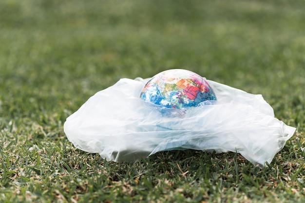 Planeta ziemia w plastikowej torbie. pojęcie zanieczyszczenia odpadami z tworzyw sztucznych. globalne ocieplenie spowodowane efektem cieplarnianym