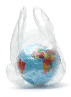 Planeta ziemia w plastikowej torbie. zanieczyszczenie naszej planety. globus w opakowaniu. pojedynczo na białym.