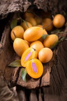 Plango owoc lub mariańska śliwkowa tropikalna południowo-wschodni asia owoc na starym drewnianym tle