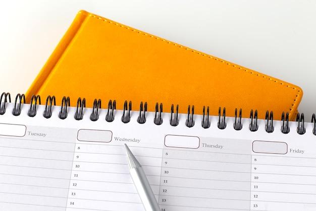 Planista na tydzień i żółty notatnik, koncepcja biznesowa