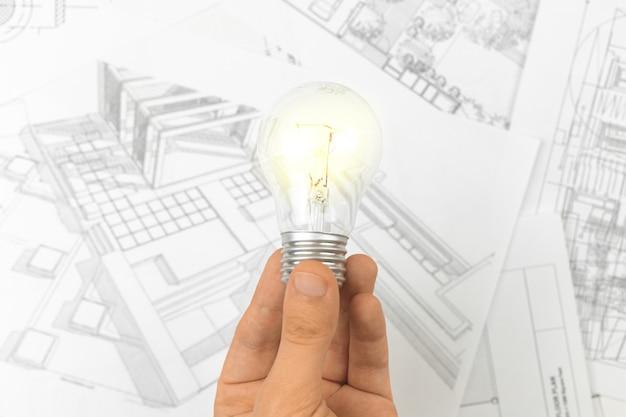 Planowanie architektoniczne za pomocą planów, koncepcja pomysłu na sukces dla budowy. mężczyzna trzyma żarówkę zdjęcie