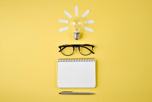 Planowanie finansowe blat z pióra, notatnik, okulary i żarówki na żółtym tle.