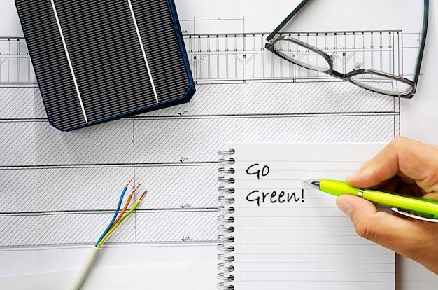 Planowanie instalacji mieszkaniowego systemu zasilania energią słoneczną na obrazie koncepcyjnym z zielonymi kablami, okularami, ogniwami słonecznymi i notatnikiem z tekstem