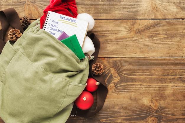 Planowanie koncepcji podróży. plecak z czapką mikołaja, paszportami i notatnikiem z listą krajów do podróży i ozdób choinkowych na drewnianym blacie