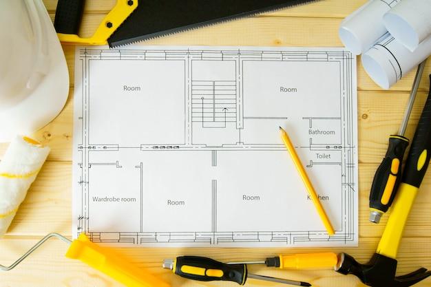 Planowanie naprawy domu. prace naprawcze. rysunki do budowy, piły, młotka i innych narzędzi na podłoże drewniane.