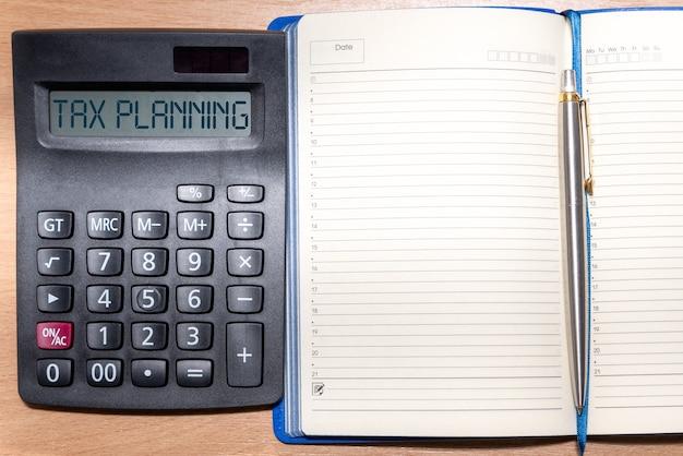 Planowanie podatkowe słowo na kalkulatorze. czas na zapłacenie podatku za rok. kalkulator, notatnik i długopis na drewnianym stole. koncepcja biznesowa i podatkowa.