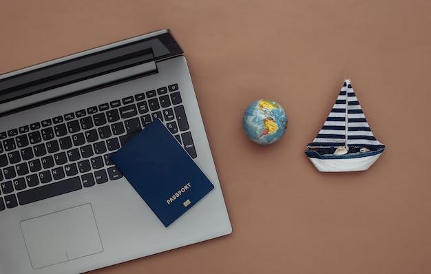 Planowanie, podróże online. laptop i żaglówka, paszport, kula ziemska na brązowym tle. widok z góry. płaskie ułożenie