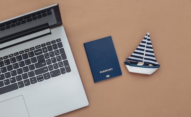 Planowanie, podróże online. laptop i żaglówka, paszport na brązowym tle. widok z góry. płaskie ułożenie