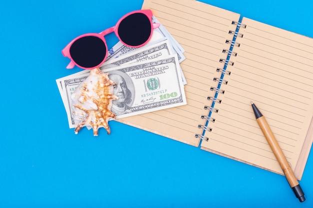 Planowanie podróży, koncepcja wakacji. na otwartym pustym notatniku leżą dolary, różowe okulary przeciwsłoneczne, długopis, muszla na niebieskim tle, widok z góry, miejsce na kopię. może być używany w tle, układ