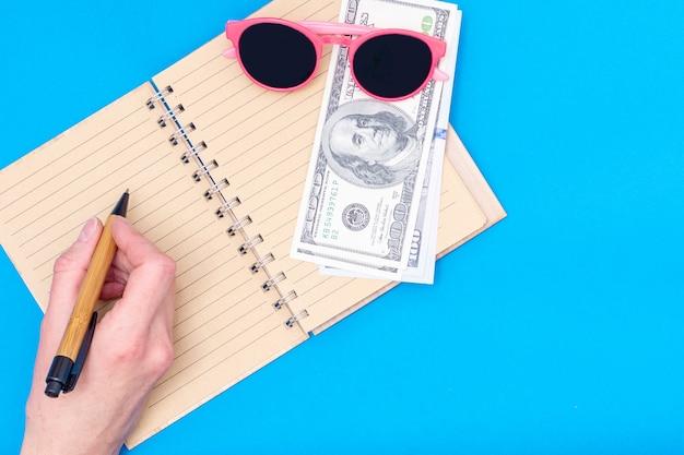 Planowanie podróży, koncepcja wakacji. ręka trzyma długopis nad otwartym zeszytem, obok leżą dolary, różowe okulary na niebieskim tle, widok z góry, miejsce na kopię. może być używany w tle, układ