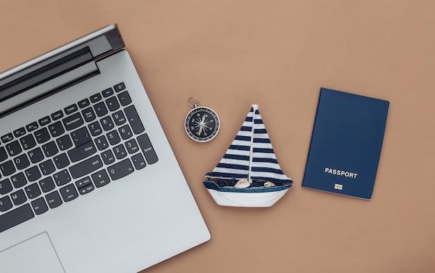 Planowanie podróży. laptop i żaglówka, kompas, paszport na brązowym tle. widok z góry. płaskie ułożenie