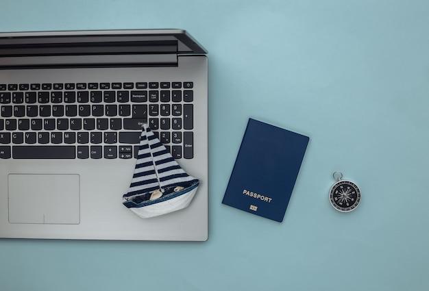 Planowanie podróży. laptop i żaglówka, kompas, paszport na niebieskim tle. widok z góry. płaskie ułożenie