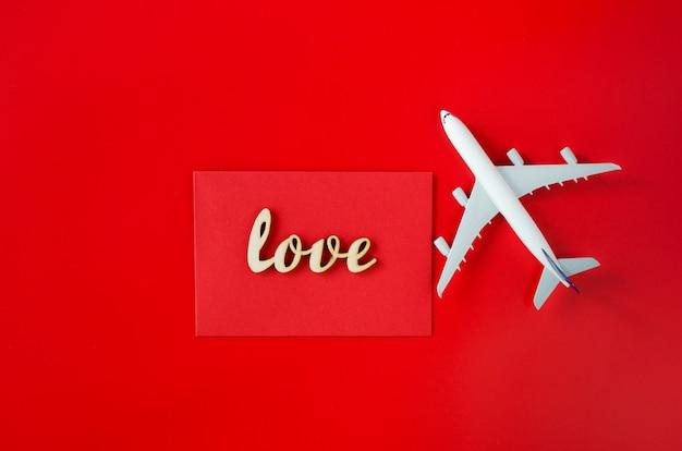 Planowanie podróży na walentynki. koncepcja podróży. napis miłość i model samolotu pasażerskiego na czerwonym tle.