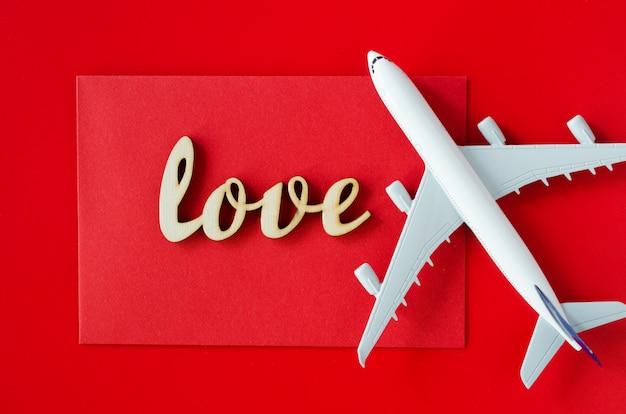 Planowanie podróży na walentynki. koncepcja podróży. napis miłość i model samolotu pasażerskiego