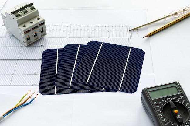 Planowanie przejścia na energię słoneczną. plan budowy lub plan budowy i ogniwa słoneczne z kalkulatorem i sprzętem elektrycznym.