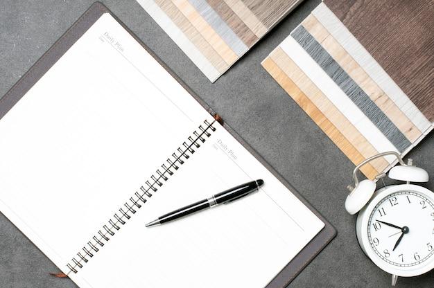 Planowanie remontu domu za pomocą próbek drewna, notatnika, długopisu i budzika
