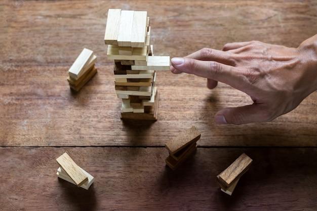 Planowanie, ryzyko i strategia w biznesie, biznesmen i inżynier hazardu umieszczenie drewnianego bloku na wieży.
