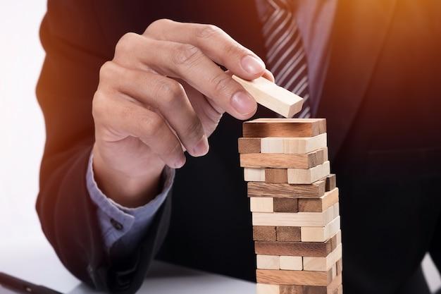 Planowanie, ryzyko i strategia w koncepcji biznesowej, biznesmen hazardu umieszczenie drewnianego bloku na wieży.