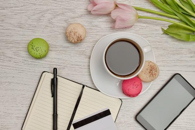Planowanie spraw. kubek kawy z deserem, notatnik, karta kredytowa i telefon komórkowy. pomysł na biznes