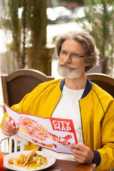Planowanie wycieczki. przemyślany brodaty mężczyzna z mapą miasta w rękach jedzący lunch i patrzący na ulicę przed chodzeniem.