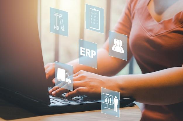 Planowanie zasobów przedsiębiorstwa (erp) ikony koncepcji zarządzania dokumentami na wirtualnym ekranie. ręce piszące na laptopie jako tło