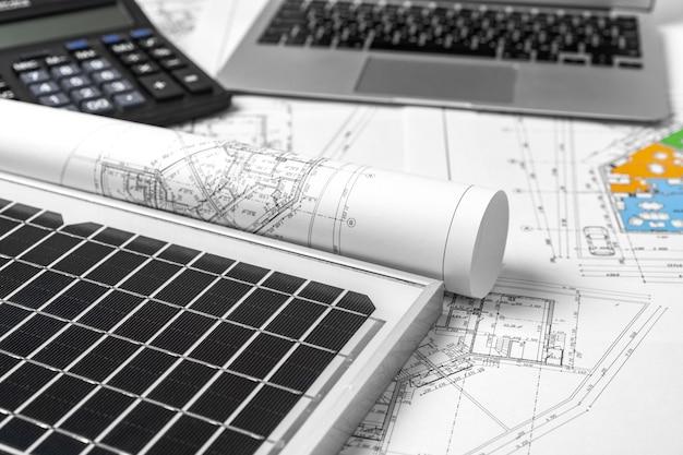 Plany architektoniczne i panel słoneczny na stole