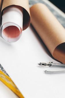 Plany architektoniczne i rolki planów oraz narzędzia do rysowania na stole roboczym.