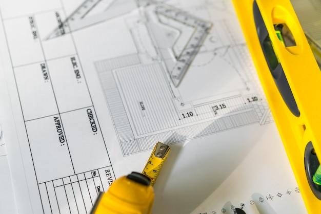 Plany budowy z kaskiem i narzędziami rysunkowymi na planach.