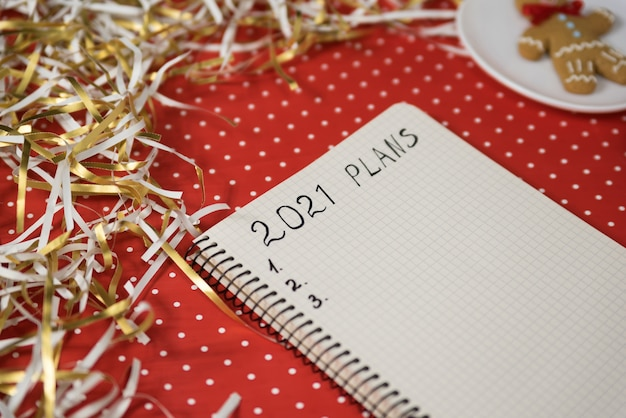 Plany na 2021 rok w zeszycie. piernika na czerwonym tle, świecidełko. koncepcja nowego roku.