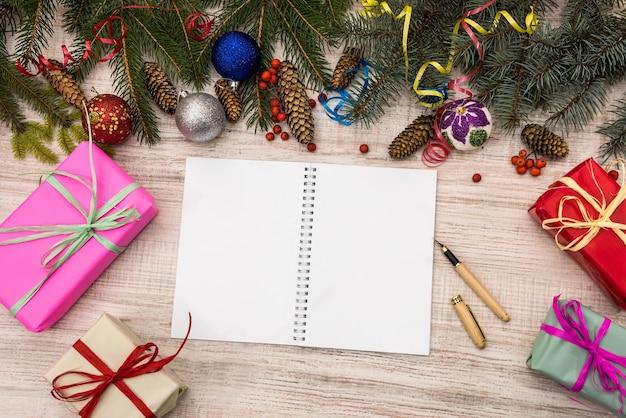 Plany na nowy rok. otwórz pamiętnik na stole z pudełkami na prezenty i gałęziami jodły