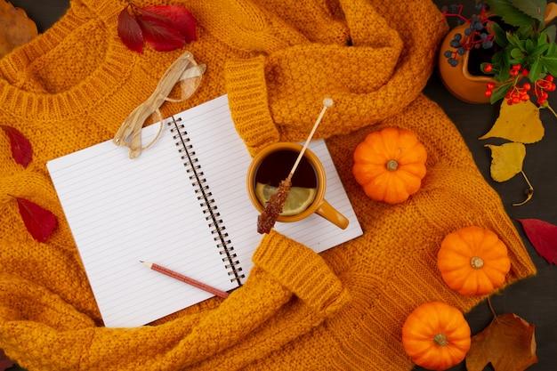 Płaska, jesienna kompozycja z jesiennymi liśćmi, gorącą filiżanką herbaty i ciepłym wełnianym pomarańczowym swetrem