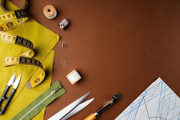 Płaska kompozycja akcesoriów do szycia, nożyczki, wzory na brązowym tle, widok z góry, miejsce na kopię.