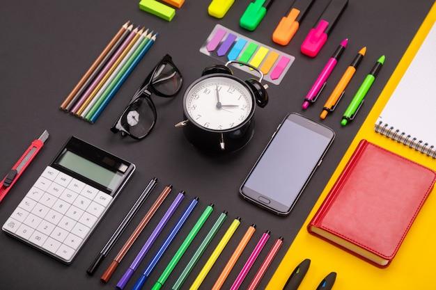 Płaska kompozycja biurka z budzikiem, smartfonem, notatnikiem, naklejkami i kolorowymi długopisami na kolorowej czerni i żółci