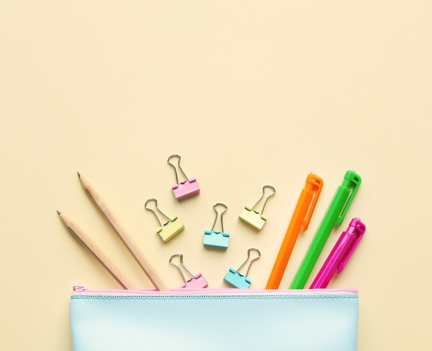 Płaska kompozycja leżąca w pastelowym niebieskim piórniku z piórami, ołówkami, segregatorami.