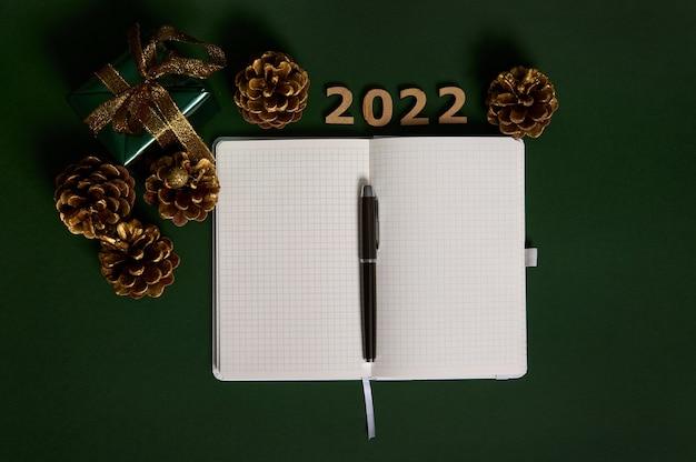 Płaska kompozycja świecka z długopisem na otwartym notatniku z pustymi pustymi białymi kartkami, luksusowy prezent świąteczny w brokatowym papierze pakowym i złotą kokardką, drewniane cyfry 2022 i sosnowe szyszki pomalowane na złoty kolor