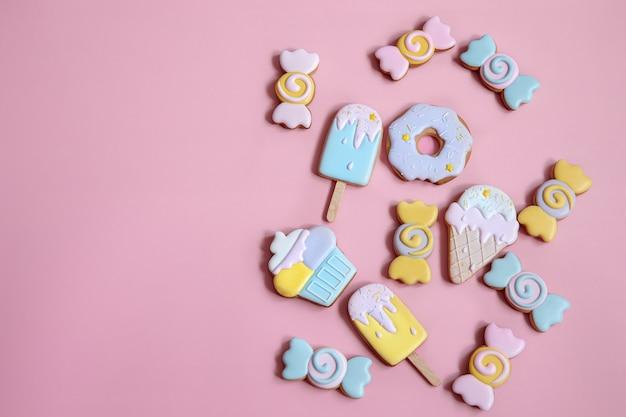 Płaska kompozycja świecka z jasnymi przeszklonymi piernikowymi ciasteczkami na różowym tle.