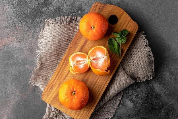 Płaska kompozycja świecka ze świeżymi pomarańczowymi mandarynkami na drewnianej desce do krojenia i ciemnym tle, widok z góry