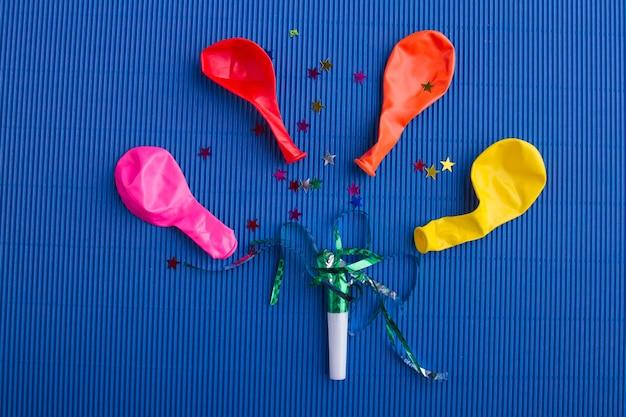 Płaska kompozycja świeckich kolorowych balonów bez powietrza z blichtrami i konfetti na niebieskim tle
