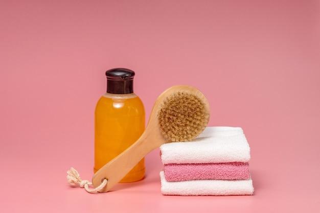 Płaska kompozycja świeckich kosmetyków spa i ręcznik na różowym tle