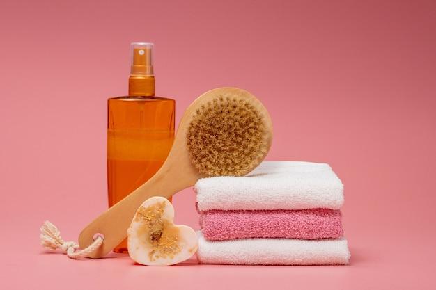 Płaska kompozycja świeckich kosmetyków spa i ręcznik na różowym tle.