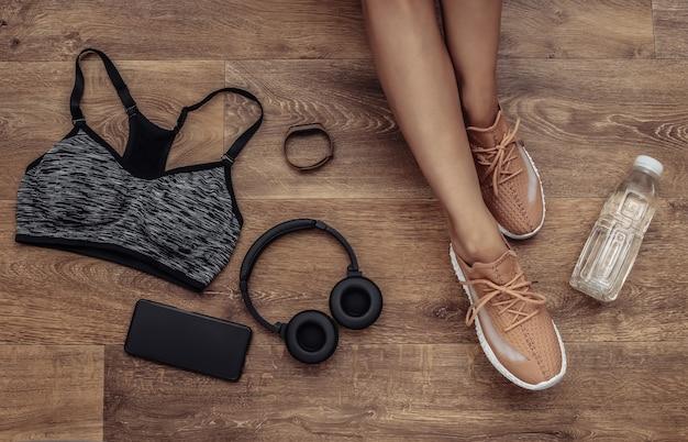 Płaska kompozycja świeckich nóg kobiety, sprzętu sportowego i ubrań na drewnianej podłodze. koncepcja fitness, sport i zdrowy styl życia. widok z góry