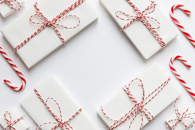 Płaska kompozycja świeckich z pudełkami na prezenty świąteczne z czerwoną wstążką, laskami cukierków na białej powierzchni, miejsce na kopię. zimowe wakacje wzór. widok z góry