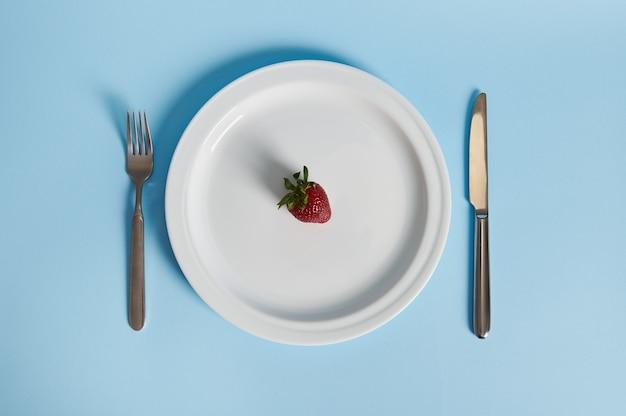 Płaska kompozycja świeckich z pyszną truskawką na talerzu, widelcu i nożu na białym tle. koncepcja zdrowego odżywiania.