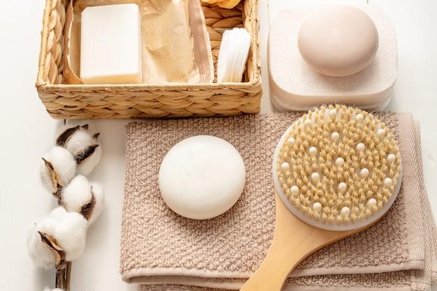 Płaska kompozycja z akcesoriami do kąpieli i pielęgnacji skóry na białej powierzchni