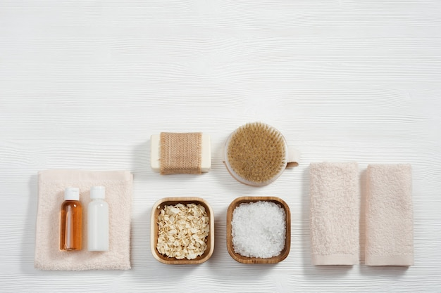 Płaska kompozycja z akcesoriami do kąpieli z bawełnianymi ręcznikami, małymi buteleczkami z żelem i szamponem z solą morską